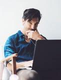 Uśmiechnięty dorosły biznesmen pracuje przy biurem Obsługuje używać współczesnego notatnika na hełmofonach w rocznika krześle pod Fotografia Stock