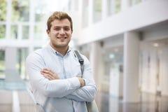 Uśmiechnięty dorosły męski uczeń w nowożytnym uniwersyteta lobby fotografia royalty free