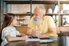 Uśmiechnięty dziad i wnuczka maluje obrazek wpólnie Obraz Stock
