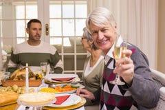 Uśmiechnięty dziadek wznosić toast przy kamerą przed jego rodziną Fotografia Royalty Free