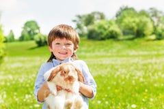 Uśmiechnięty dzieciak z ślicznym królikiem w lecie Fotografia Stock