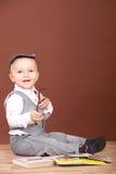 Uśmiechnięty dziecka obsiadanie na podłoga z książkami, patrzeje kamerę Obraz Royalty Free