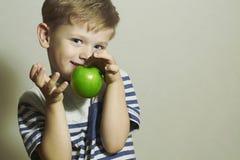 Uśmiechnięty dziecko z Zielonym jabłkiem Mała Przystojna chłopiec zdrowy owoce Fotografia Royalty Free