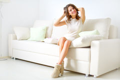 Uśmiechnięty dziewczyny obsiadanie na kanapie Obrazy Stock