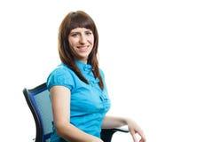 Uśmiechnięty dziewczyny obsiadanie na krześle fotografia stock