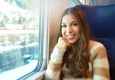 Uśmiechnięty dziewczyny podróżowanie w pociągu z zima śniegu krajobrazem z okno patrzeje kamerę obrazy royalty free