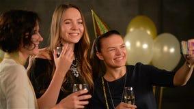Uśmiechnięty dziewczyny Use Cyfrowego gadżet brać fotografię przy przyjęciem na Czarnym tle z Lotniczymi balonami Młode Kobiety z zbiory wideo