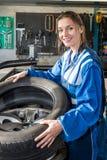 Uśmiechnięty Żeński mechanik Wspina się Samochodową oponę Na obręczu W garażu zdjęcia royalty free