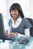 Uśmiechnięty elegancki bizneswoman pracuje na komputerze Zdjęcia Stock