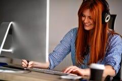 Uśmiechnięty elegancki projektant jest ubranym hełmofony i działanie na t fotografia royalty free