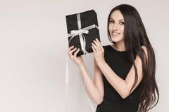 Uśmiechnięty eleganckiej kobiety mienia prezent Fotografia Royalty Free