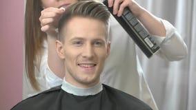 Uśmiechnięty facet przy fryzjerem męskim zdjęcie wideo