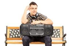 Uśmiechnięty facet trzyma boombox sadzający na drewnianej ławce Fotografia Stock