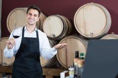 Uśmiechnięty fachowy mężczyzna sprzedawca w fartuch pozyci w sklepie fotografia royalty free