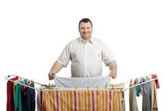 Uśmiechnięty gruby mężczyzna w koszulowej suszarniczej pralni Obrazy Stock