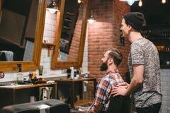 Uśmiechnięty hairstylist i plesed mężczyzna klient patrzeje w lustrze obrazy stock