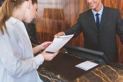 Uśmiechnięty hotelowy pracownik pomaga jego gościa Obrazy Stock