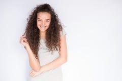 Uśmiechnięty i szczęśliwy młodej kobiety spojrzenie przy jeden stroną z kędzierzawym włosy Zdjęcia Stock