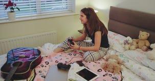 Uśmiechnięty i szczęśliwy nastolatek dziewczyny bawić się koncentrował na PlayStation, przyśpiesza relaksującego czas po ciężkieg zbiory wideo