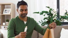 Uśmiechnięty indyjski mężczyzna odpakowywa takeaway jedzenie w domu zbiory