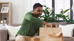 Uśmiechnięty indyjski mężczyzna odpakowywa takeaway jedzenie w domu zbiory wideo