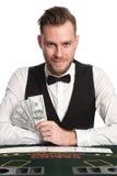 Uśmiechnięty kasynowy handlowiec z pieniądze Fotografia Stock