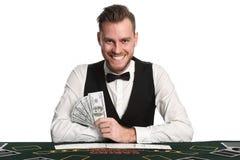 Uśmiechnięty kasynowy handlowiec z pieniądze Obraz Royalty Free