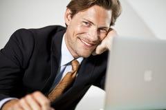 Uśmiechnięty Kaukaski biznesmen używa laptop obrazy royalty free