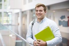 Uśmiechnięty Kaukaski męski uczeń w nowożytnym uniwersyteckim budynku Obrazy Stock