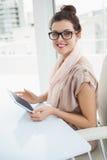 Uśmiechnięty kauzalny bizneswoman używa pastylkę obraz royalty free