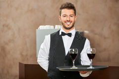 Uśmiechnięty kelner porci czerwone wino w restauraci Fotografia Royalty Free
