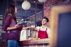 Uśmiechnięty kelner słuzyć klienta Obrazy Stock