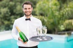 Uśmiechnięty kelner trzyma szampańskich flety i butelkę Zdjęcie Stock