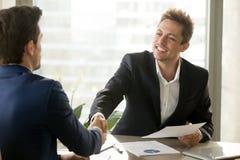 Uśmiechnięty kierownika i klienta handshaking, oferuje pieniężnego contr zdjęcia royalty free