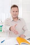 Uśmiechnięty kierownika obsiadanie przy biurem - przygotowywającym dla ręki chwiania. obraz royalty free