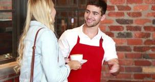 Uśmiechnięty klient płaci kredytową kartą zbiory