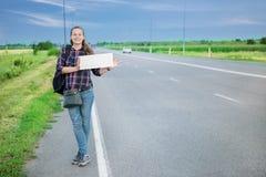 Uśmiechnięty kobieta autostopowicz na drodze trzyma pustą deskę obrazy stock
