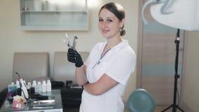 Uśmiechnięty kobieta dentysta trzyma stomatologicznych traktowań narzędzia w jej rękach, zwolnione tempo zbiory wideo