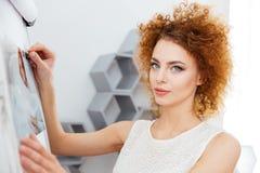 Uśmiechnięty kobieta fotograf stawia fotografie na whiteboard w biurze Obrazy Stock