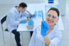 Uśmiechnięty kobieta naukowiec patrzeje tubki z rezultatami analiza obrazy royalty free