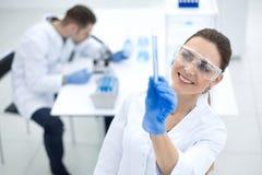 Uśmiechnięty kobieta naukowiec patrzeje tubki z rezultatami analiza fotografia royalty free