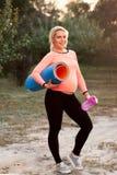 Uśmiechnięty kobieta w ciąży przygotowywający dla sprawności fizycznej plenerowej zdjęcia royalty free