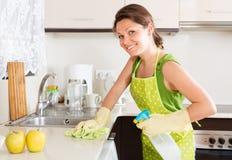 Uśmiechnięty kobiety cleaning meble w kuchni Zdjęcia Stock