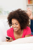 Uśmiechnięty kobiety czytać sms na jej wiszącej ozdobie Obraz Stock