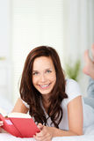Uśmiechnięty kobiety czytanie w łóżku Obrazy Stock