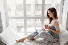 Uśmiechnięty kobiety gawędzenie na laptopie zdjęcia stock