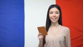 Uśmiechnięty kobiety mienia paszport przeciw francuz flagi tłu, podróż za granicą zdjęcie wideo