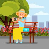 Uśmiechnięty kobiety obsiadanie na drewnianej ławki i robić selfie Zielony drzewo, kwitnący kwiaty i miasto budynki na tle royalty ilustracja