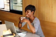 Uśmiechnięty kobiety pić kawowy i patrzeć laptop Obrazy Royalty Free