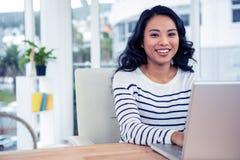 Uśmiechnięty kreatywnie bizneswoman używa laptop Obraz Stock